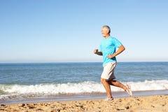 Homme aîné exécutant le long de la plage Photo stock