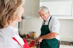 Homme aîné faisant cuire dans la cuisine Images libres de droits