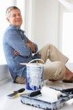 Homme aîné faisant la pause de décorer la maison Images libres de droits