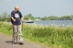 Homme aîné faisant une promenade nordique un jour ensoleillé. Image libre de droits