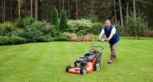 Homme aîné fauchant la pelouse. Photographie stock