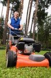 Homme aîné fauchant la pelouse. Photos libres de droits