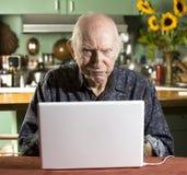 Homme aîné grincheux avec un ordinateur portable Photos stock