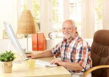 Homme aîné heureux à l'aide de l'ordinateur Images libres de droits