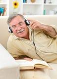 Homme aîné heureux écoutant la musique Images stock