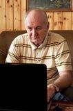 Homme aîné heureux avec l'ordinateur portatif Image stock