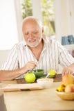 Homme aîné heureux ayant le thé dans la cuisine Images libres de droits