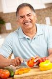 Homme aîné heureux coupant des légumes Photo stock