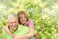 Homme aîné heureux donnant sur le dos Photos stock
