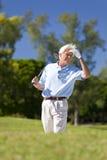 Homme aîné heureux jouant au golf recherchant sa bille Photographie stock libre de droits