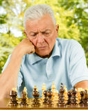 Homme aîné inquiété jouant aux échecs Images libres de droits