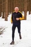 Homme aîné Joggin dans la neige Photographie stock libre de droits