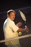Homme aîné jouant au tennis Photographie stock