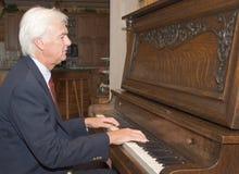 Homme aîné jouant le piano Image stock