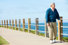 Homme aîné marchant le long du chemin par la mer Photo libre de droits