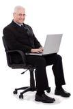 Homme aîné occupé d'affaires s'asseyant dans la présidence Images stock