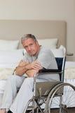 Homme aîné pensif dans son fauteuil roulant Images stock