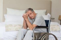 Homme aîné pensif dans son fauteuil roulant Image libre de droits