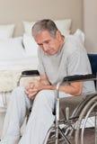 Homme aîné pensif dans son fauteuil roulant Images libres de droits