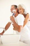 Homme aîné rasant dans la salle de bains avec l'observation d'épouse Photos libres de droits