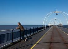 Homme aîné regardant à l'extérieur au-dessus de la plage Southport Image stock