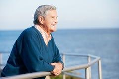 Homme aîné regardant au-dessus de la clôture la mer Image stock