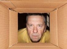 Homme aîné regardant fixement dans la boîte en carton Photos stock