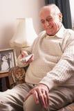 Homme aîné regardant la TV à la maison Photo stock