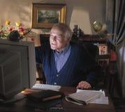 Homme aîné regardant le contenu apparaissant d'ordinateur Photographie stock