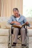 Homme aîné regardant son album photos Images stock