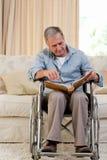 Homme aîné regardant son album photos Images libres de droits