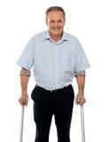 Homme aîné restant avec le support des béquilles Photos stock