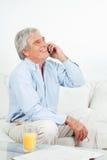 Homme aîné riant au téléphone Image libre de droits