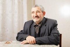 Homme aîné s'asseyant à la table Photographie stock