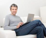 Homme aîné s'asseyant dans le sofa et à l'aide de l'ordinateur portatif Photos stock