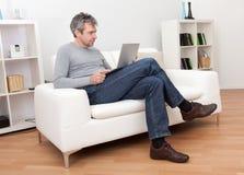 Homme aîné s'asseyant dans le sofa et à l'aide de l'ordinateur portatif Image libre de droits