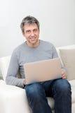 Homme aîné s'asseyant dans le sofa et à l'aide de l'ordinateur portatif Photo stock