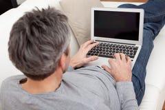 Homme aîné s'asseyant dans le sofa et à l'aide de l'ordinateur portatif Image stock