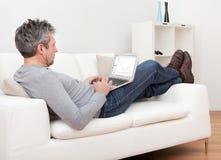 Homme aîné s'asseyant dans le sofa et à l'aide de l'ordinateur portatif Photo libre de droits