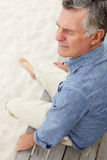 Homme aîné s'asseyant par la plage Photos stock