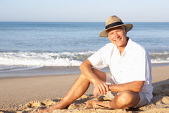 Homme aîné s'asseyant sur la détente de plage Images libres de droits