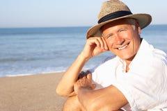 Homme aîné s'asseyant sur la détente de plage Images stock