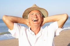 Homme aîné s'asseyant sur la détente de plage Image libre de droits