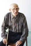 Homme aîné s'asseyant sur la présidence Photographie stock libre de droits