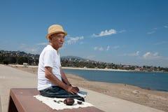 Homme aîné s'asseyant sur un banc Photos libres de droits