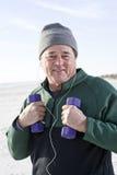 Homme aîné s'exerçant avec des poids de main sur la plage Photo libre de droits