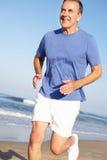 Homme aîné s'exerçant sur la plage Photo stock