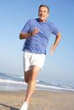 Homme aîné s'exerçant sur la plage Image stock