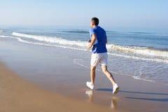 Homme aîné s'exerçant sur la plage Photos libres de droits