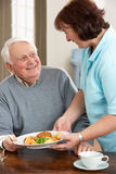 Homme aîné servi le repas par Carer Photo stock